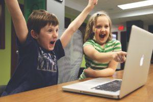 enfants devant un ordinateur qui réussissent